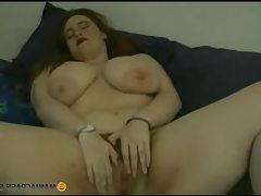 Chubby woman lies and licks her titties